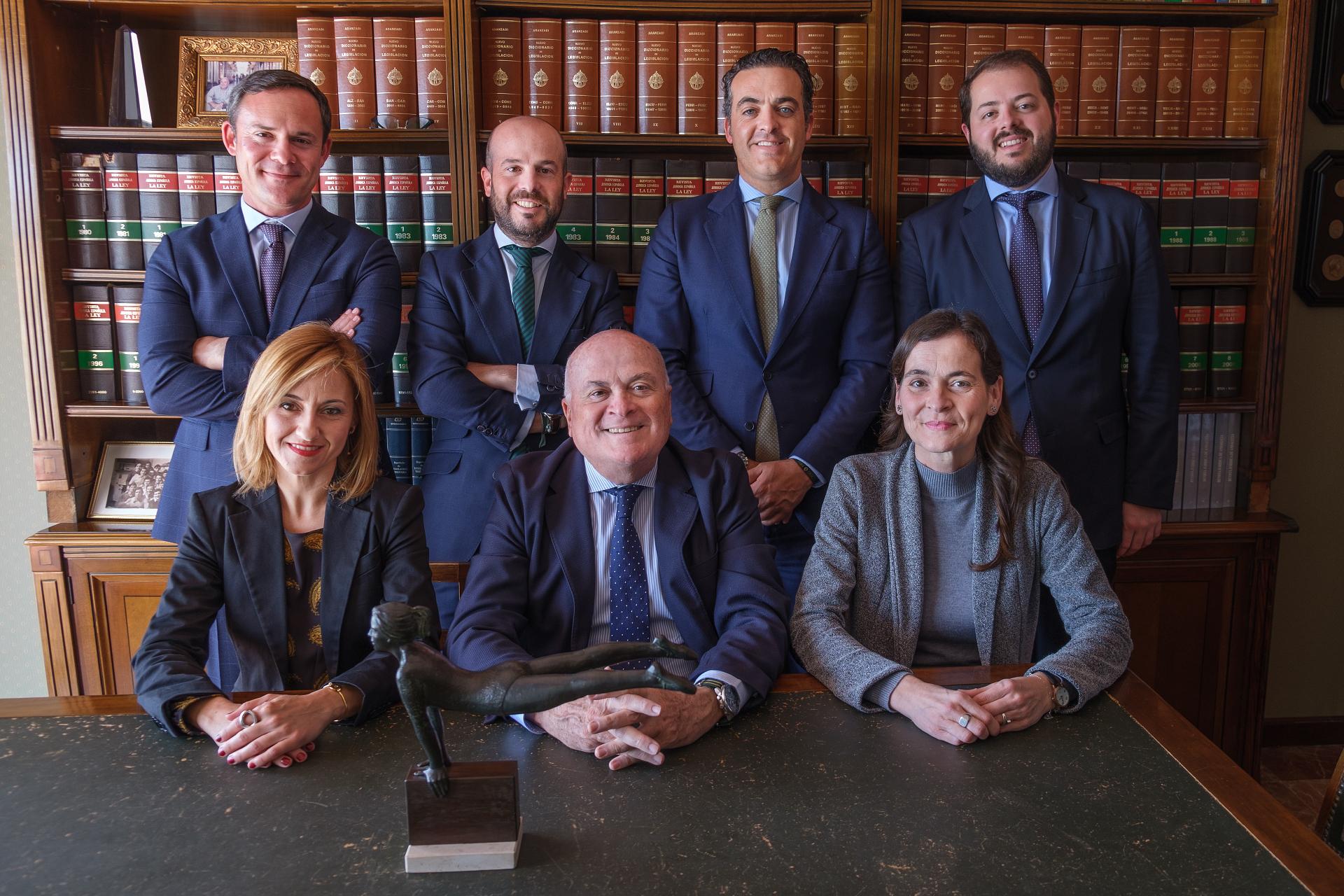 Foto de grupo de todo el equipo de AIC ABOGADOS en la biblioteca del despacho